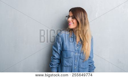 Young adult woman over grunge grey wall wearing glasses looking away to side with smile on face, natural expression. Laughing confident.