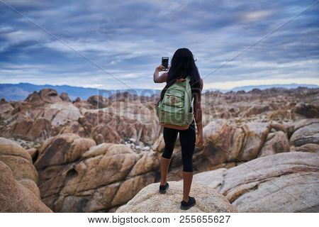 woman taking photo of boulders at alabama hills with smartphone
