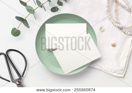 stack of blank business cards on a white feminine styled desk with mint bowl, decorative scissors, linen napkin and eucalyptus twigs. minimalist mock up, flat lay / top view
