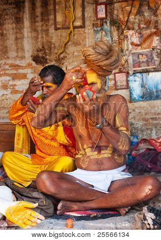 KATHMANDU, NEPAL -  OCTOBER 27 : Two Shaiva sadhus (holy man) do makeup in the colonnade of the temple Pashupatinath on October 27, 2010 in Kathmandu valley, Nepal.