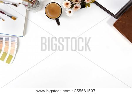 Top View Office Desk With Designer Table A Pantone, Coffee And Notebook Paper Sketch On White Table