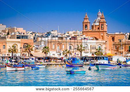 Marsaxlokk, Malta. Luzzu Traditional Eyed Colorful Boats In The Harbor Of Fishing Village, Mediterra