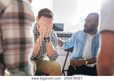 Unhappy Man Hiding His Face And Crying While Being At Psychological Session
