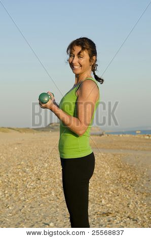 A happy woman exercising with dumbells.