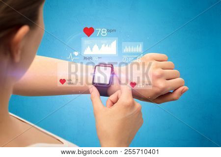 Female hand with smartwatch and health application icons nearby.