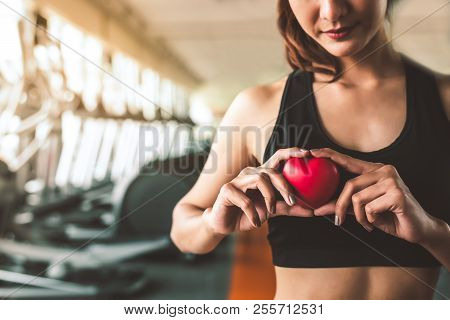 Happy Sport Woman Holding Red Heart In Fitness Gym Club. Medical Cadio Heart Strength Training Lifes