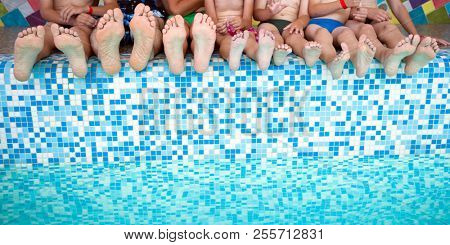 Group of people legs while sitting on edge of swimming pool. Feet of group of friends or parents with children on edge of swimming pool