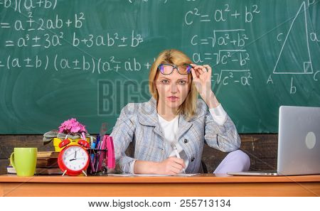 She Has Doubts In Your Report Or Knowledge. Teacher Suspiciously Peeking Out Of Eyeglasses. Teacher