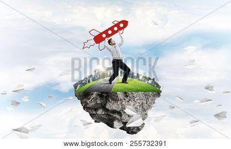 Young confident businessman in suit launching big rocket from his hand while standing among flying paper planes on the flying island with cloudy skyscape view on background. poster