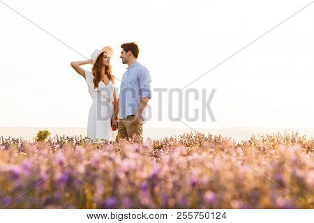 Photo of beautiful young people dating and walking together outdoor in lavender field