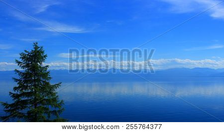 A Quiet Summer Landscape On Lake Baikal In Blue Tones. The Sky And Calm Water Of The Lake Merge On T
