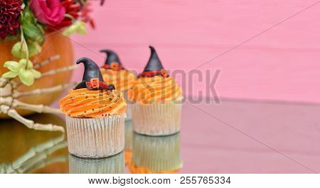 Halloween cupcakes background. Witches hat cupcake. Halloween treats on wooden pink background with palm of skeleton. Halloween pumpkin with Halloween monsters cupcake. Halloween background. Halloween monsters party cupcake. Halloween background Halloween