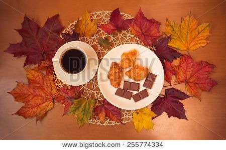 Сup Of Coffee, Chocolate, Croissants And Autumn Maple Leaves On Wooden Table. Top View.