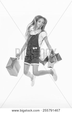 Happy Child Jump With Shopping Bags Isolated On White. Little Girl Smile With Paper Bags. Kid Shoppe