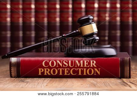 Gavel And Soundboard On Consumer Protection Law Book Over Wooden Table