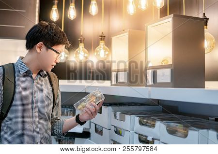 Young Asian Man Choosing Package Of Electrical Light Bulb In The Store. Furniture Home Decoration Sh