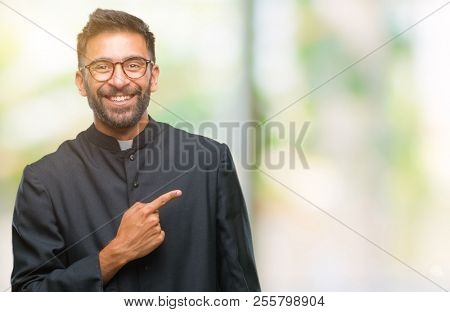 Adult hispanic catholic priest man over isolated background cheerful with a smile of face pointing with hand and finger up to the side with happy and natural expression on face looking at the camera.