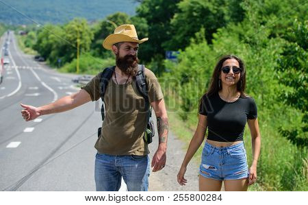 Couple Travelers Man And Girl Hitchhiking At Edge Road Nature Background. Travellers Try To Stop Car