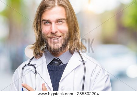 Young handsome doctor man with long hair over isolated background cheerful with a smile of face pointing with hand and finger up to the side with happy and natural expression on face