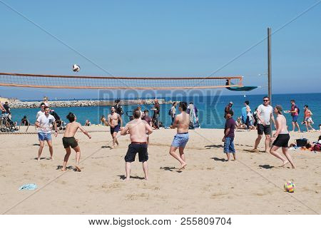 BARCELONA, SPAIN - APRIL 17, 2018: Men play volleyball on the beach. The City is the Capital of Catalonia.