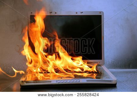 Laptop Damage. Laptop on fire and flames. Computer Repair. Flaming Fire laptop computer.