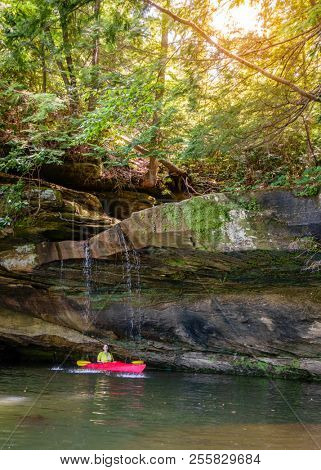 Kayaker behind a small waterfall on Grayson Lake in Kentucky