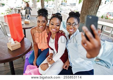 Three Casual African American Girls With Colored Shopping Bags Walking Outdoor. Stylish Black Womans