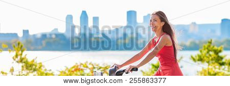 City lifestyle young urban woman riding bike in park, with downtown skyline in the background. Summer activity active living, Asian girl biking outdoors. Bicycle sport banner panorama.