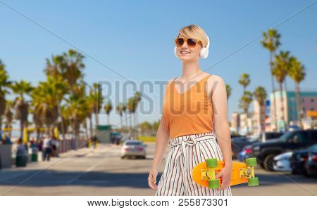 sport, leisure and skateboarding concept - smiling teenage girl in sunglasses and headphones with short modern cruiser skateboard over venice beach background in california