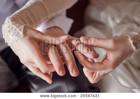 Bride putting a ring on groom's finger during wedding ceremony
