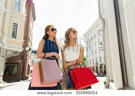 sale, consumerism and people concept - happy young women with shopping bags at storefront
