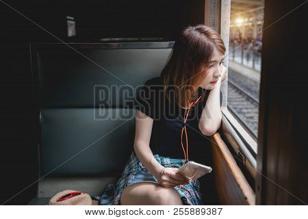 Female Passenger Listening Music, Traveling By Train Looking Out Window. Young Tourist Woman Using S