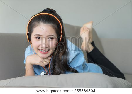 Girl Listening Music Headphones Lying On Sofa At Home. Young Asian Woman Happy Smiling Face With Den