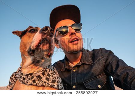 Spoiled Self Portrait Concept: Man Trying To Make A Selfie With His Funny Dog. Young Male Person And