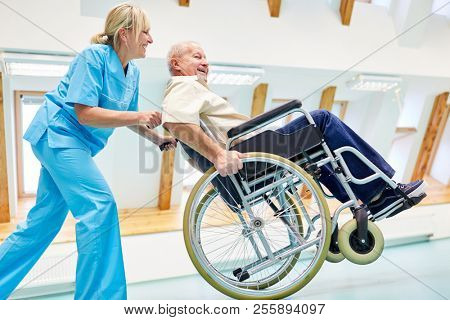 Caregiver and senior in a wheelchair silly around in retirement home or rehab