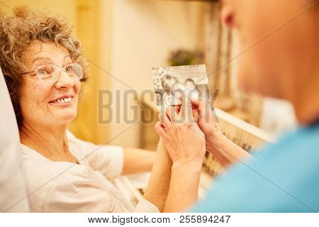 Caregiver shows senior woman with dementia an old photo as a memory workout