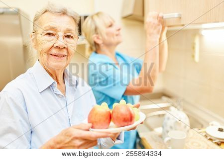 Old woman with a plate of fruit in the kitchen together with a care assistant