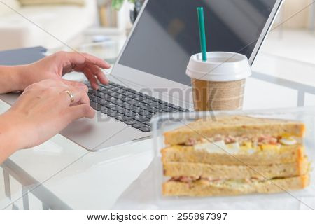 Woman eating a breakfast sandwich and drinking coffee while working with a laptop