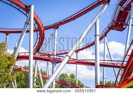 Rollercoaster In Red Colors With Curves And Loops Under A Blue Sky