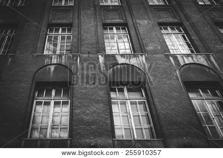 Dark Building With Tall Windows In Weathered Conditions Looking Spooky