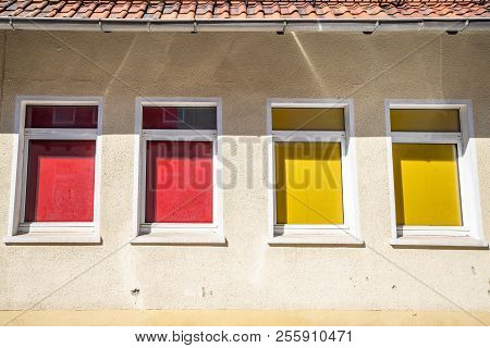 Four Colorful Windows On A Building With Red And Yellow Curtains