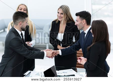 handshake business partners after discussion of the contract