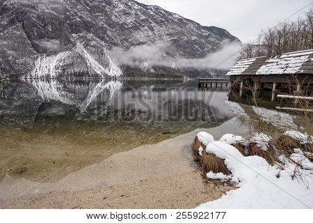Beautiful Winter Lake Bohinj With Wooden Pier And Mountains In Background Reflecting In The Water.