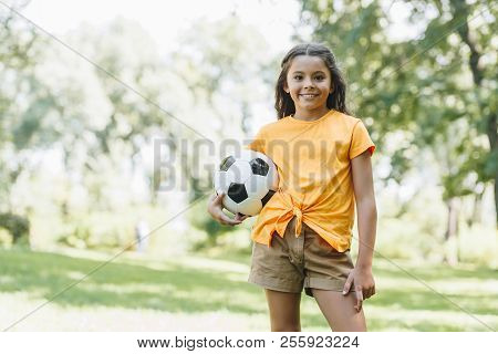 Beautiful Happy Kid Holding Soccer Ball And Smiling At Camera In Park