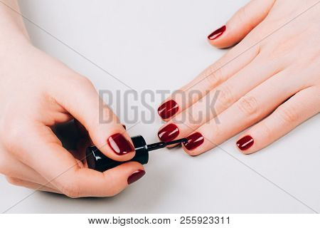 Woman Making Red Manicure By Herself On Grey Background.