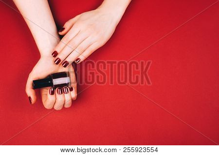 Woman Holding Manicure Bottle On Red Background.