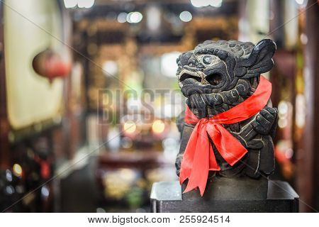 Smart black stone lion statue glance at the right side, red scarf and blur background poster