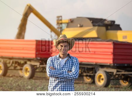Handsome Farmer With Straw Standing With Crossed Arms In Front Of Combine Harvester And Trailers Dur