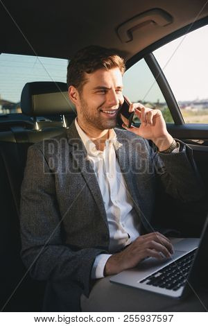 Image of successful director man in suit talking on smartphone and working on laptop while back sitting in business class car