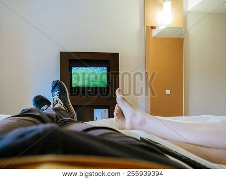 Barcelona, Spain - Jun 3, 2018: Crop Shot Of Legs Of Man And Woman Chilling On Bed In Hotel And Watc